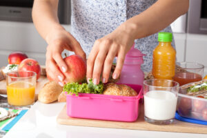 woman putting food in lunchbox